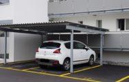 Ein Carport aus Stahl mit einem parkierten Auto darunter